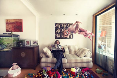 Philippe Roy is sitting in the living room calmly reading his newspaper when his daughter flies around like a superhero. Shanghai photographer with studio creates lifestyle fashion photography for advertising and marketing materials.